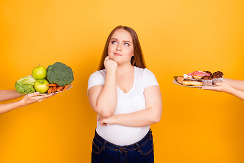 Kvinne som står mellom valget av godteri eller frukt og grønt