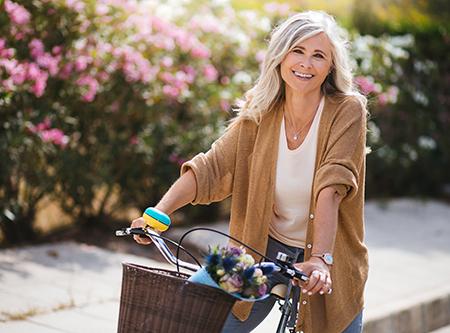 Kvinne på sykkel i solskinn