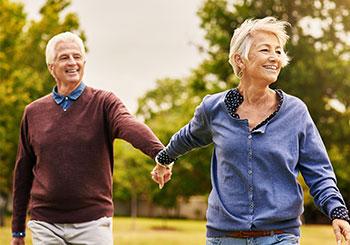 Smilende eldre par på tur i naturen